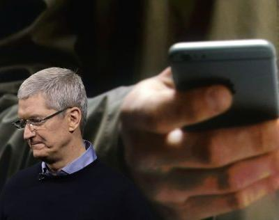 Tim Cook said Apple will reduce hiring in certain divisions because of the iPhone sales slowdown