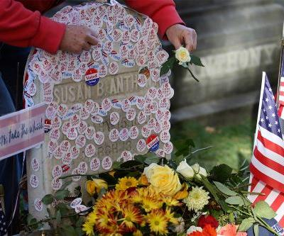 Women placing 'I voted' stickers on Susan B. Anthony's grave