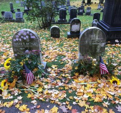 Women sharing 'I voted' stickers on Susan B. Anthony's grave