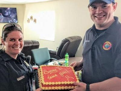 Police officer extends apology cake after mistakenly using weapon on firefighter