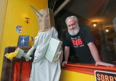 Storefront display depicting Lady Liberty with a paper bag over her head elicits threats