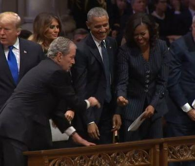 President George W. Bush hands piece of candy to Michelle Obama ahead of father's funeral