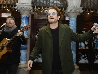 Watch Bono & The Edge Play Christmas Songs While Busking To Benefit The Homeless