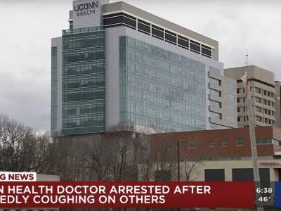 A Connecticut doctor has been charged after authorities said he deliberately coughed on his coworkers
